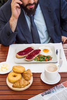 Homem, levando, ligado, telefone móvel, enquanto, tendo, pequeno almoço