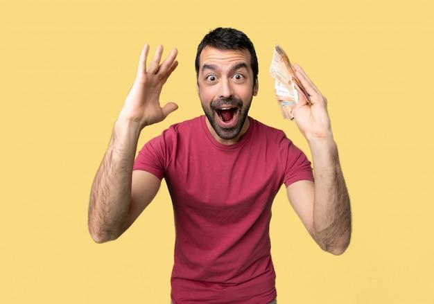 Homem levando muito dinheiro com surpresa e expressão facial chocada