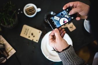 Homem, levando, quadro, de, café, e, bolo, com, seu, telefone