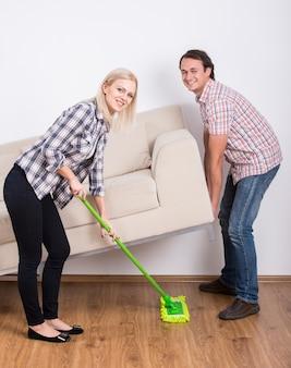 Homem levanta o sofá enquanto a garota limpa.