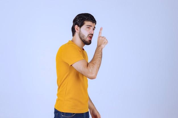Homem levantando a mão e apontando para algo acima