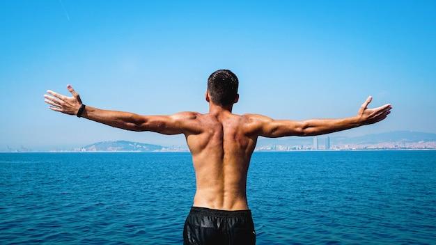 Homem levantando as mãos ou braços abertos em pé para trás olhando para o horizonte de céu azul do mar. homens fortes e musculosos, corpo, braços e costas perfeitos. conceito de liberdade