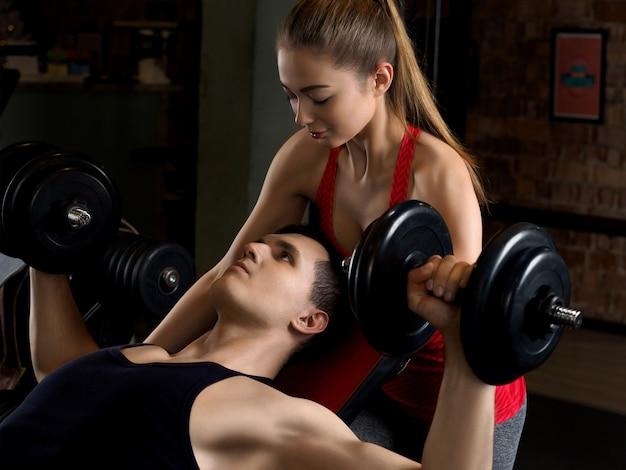 Homem levantando halteres com seu personal trainer na academia.