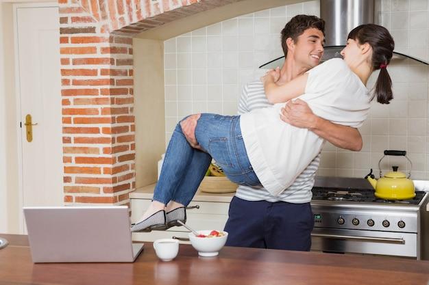 Homem levantando mulher nos braços na cozinha
