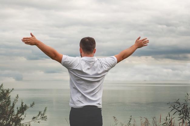 Homem levantando os braços por um lago