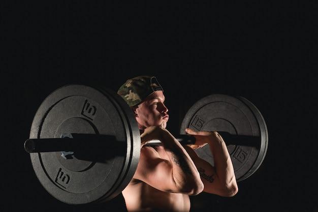 Homem levantando pesos. treino de homem musculoso no ginásio fazendo exercícios com barra