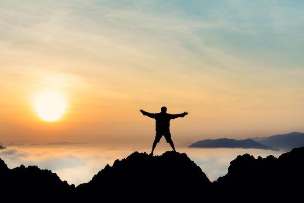 Homem liberdade, com, braços abertos, silueta, em, amanhecer, ligado, topo, montanha, céu, nevoeiro, fundo