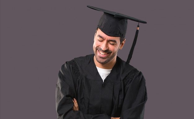 Homem, ligado, seu, dia de formatura, universidade, mantendo, a, braços cruzaram, enquanto, sorrindo, ligado, violeta, fundo