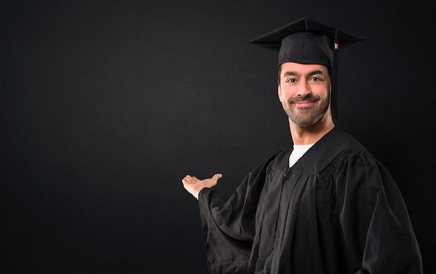 Homem, ligado, seu, dia graduação, universidade, apontar, costas, com, a, dedo indicador, apresentando, um, prod