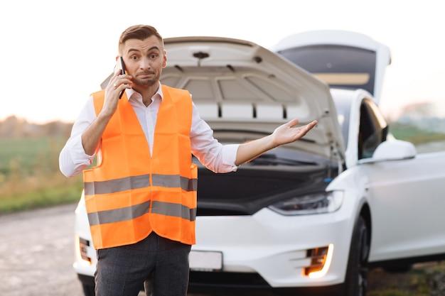 Homem ligando para o serviço de assistência automóvel porque o carro elétrico está quebrado