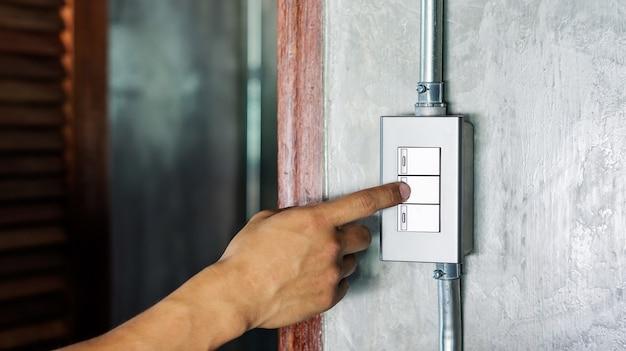 Homem ligar ou desligar em um interruptor de luz.