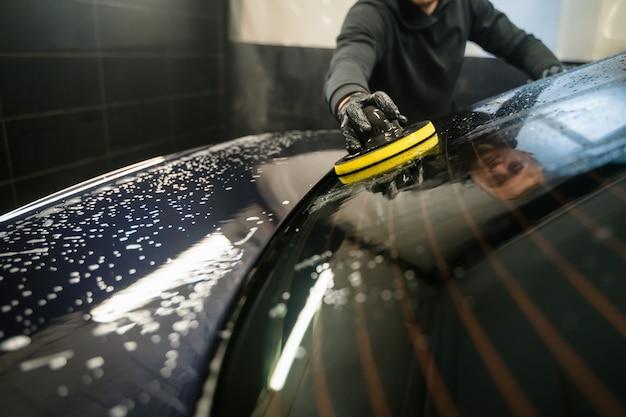 Homem limpa a janela traseira do carro com a esponja do círculo.