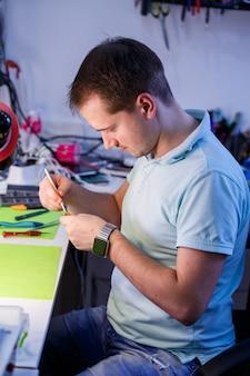 Homem limpa a poeira de um laptop com uma ferramenta especial. reparação e manutenção de laptops e pcs serviços de publicidade para a reparação de eletrônicos e dispositivos.