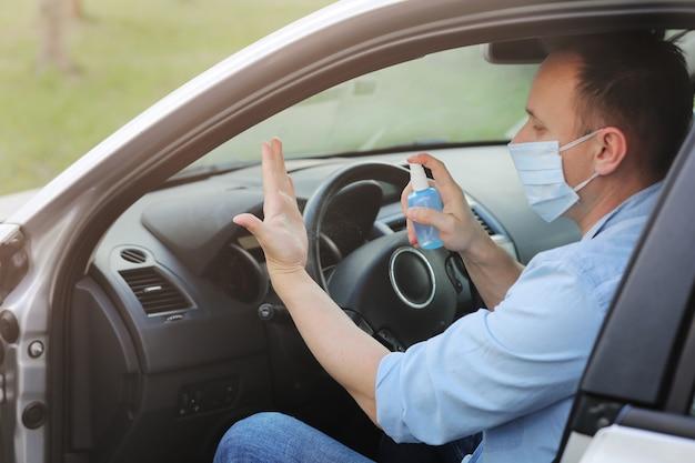 Homem limpa as mãos com spray antibacteriano antes de viajar. conceito de controle de infecção. prevenir o coronavírus, covid-19, gripe. foco seletivo