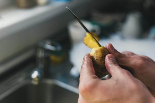 Homem limpa batatas com uma faca na pia em casa. descasque batatas pequenas. limpeza na pia.