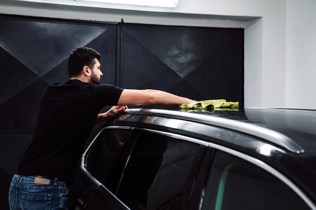 Homem limpa o corpo do carro com uma toalha.