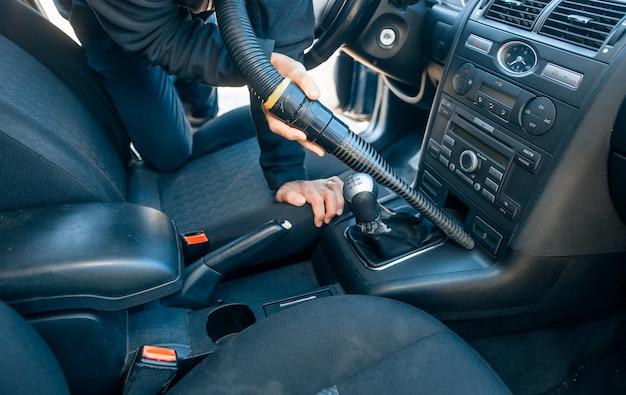 Homem limpando, aspirando o interior do carro com aspirador de pó, conceito de transporte