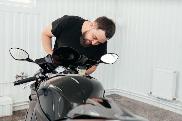 Homem limpando moto moderna bmw preta sportbike poderosa