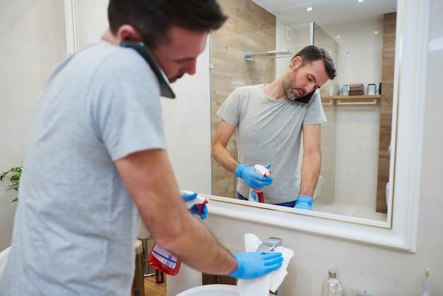 Homem limpando o banheiro e falando ao celular