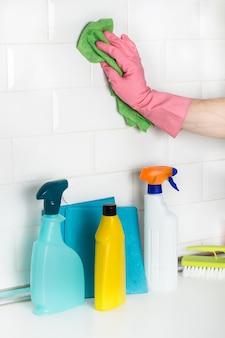 Homem limpando uma parede de azulejos brancos do metrô com um pano de esponja em uma visão de perto