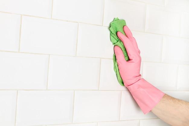 Homem limpando uma parede de ladrilhos brancos do metrô com um pano de esponja