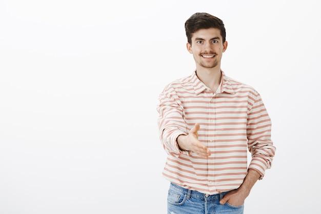Homem limpo e educado cumprimentando o novo empregador. retrato de um modelo masculino simpático e bonito, com bigode e barba, apertando a mão em um aperto de mão e dando as boas-vindas ao recém-chegado sobre a parede cinza