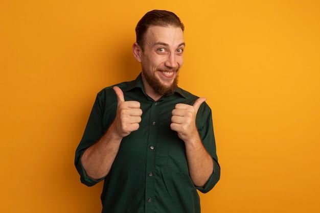 Homem loiro bonito animado com o polegar para cima olhando para a câmera em laranja