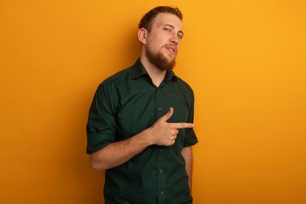 Homem loiro bonito e desagradável apontando para o lado na laranja