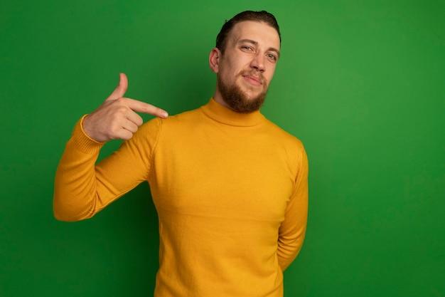 Homem loiro bonito e descontente apontando para um lado isolado na parede verde