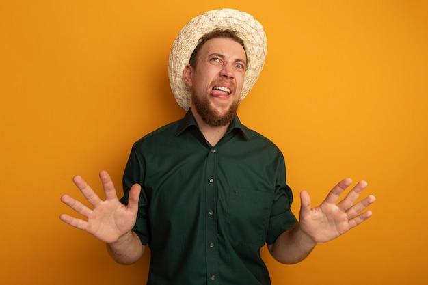 Homem loiro bonito e descontente com chapéu de praia tira a língua e mantém as mãos abertas, isolado na parede laranja