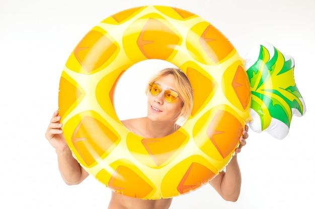 Homem loiro bonito espreita um círculo de natação em forma de abacaxi em um fundo branco