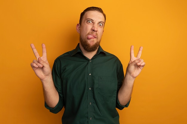 Homem loiro bonito irritado com a língua para fora e gesticulando sinal de vitória com as duas mãos isoladas na parede laranja