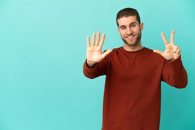 Homem loiro bonito isolado contando oito com os dedos