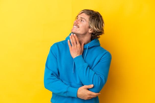 Homem loiro bonito isolado em um fundo amarelo, olhando para cima enquanto sorri