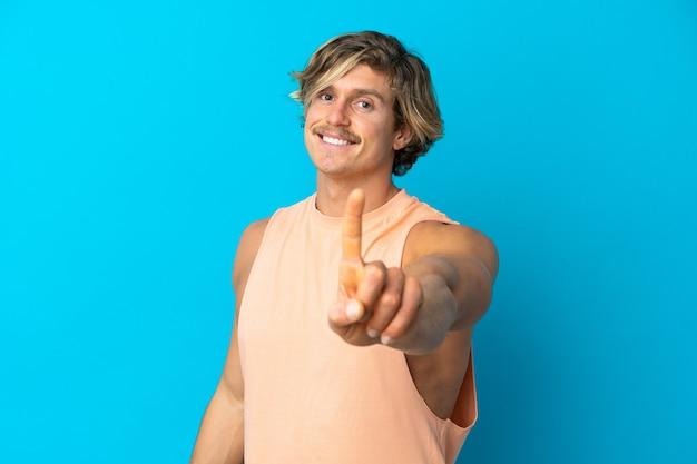 Homem loiro bonito isolado mostrando e levantando um dedo