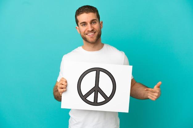 Homem loiro bonito isolado segurando um cartaz com o símbolo da paz e apontando-o