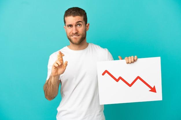Homem loiro bonito isolado segurando uma placa com um símbolo de seta de estatísticas decrescentes e cruzando os dedos
