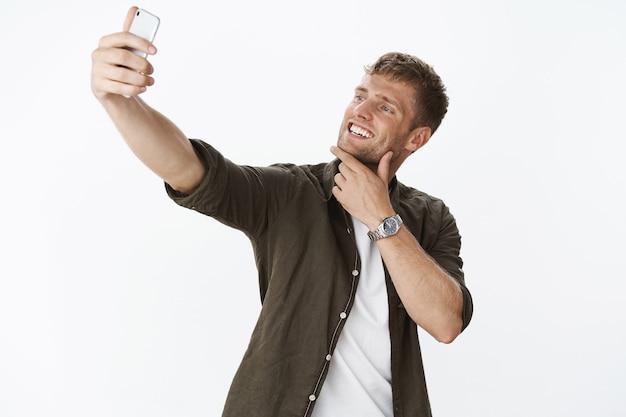 Homem loiro bonito jovem e elegante tocando o queixo e sorrindo amplamente enquanto estendia a mão para tirar selfie no smartphone fazendo careta, posando sobre uma parede cinza encantado