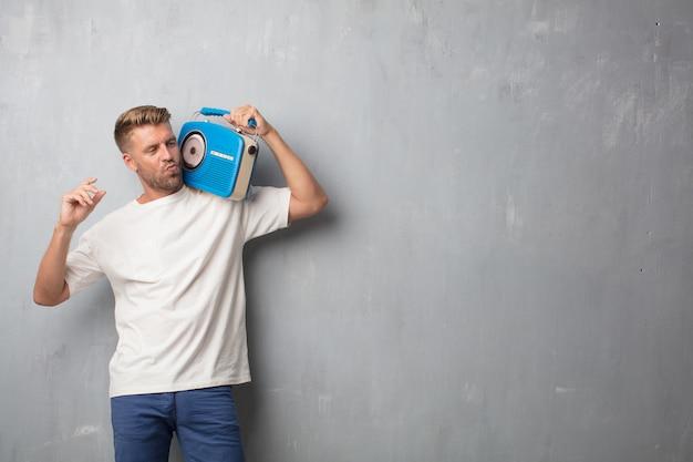 Homem loiro bonito ouvir música com um rádio vintage