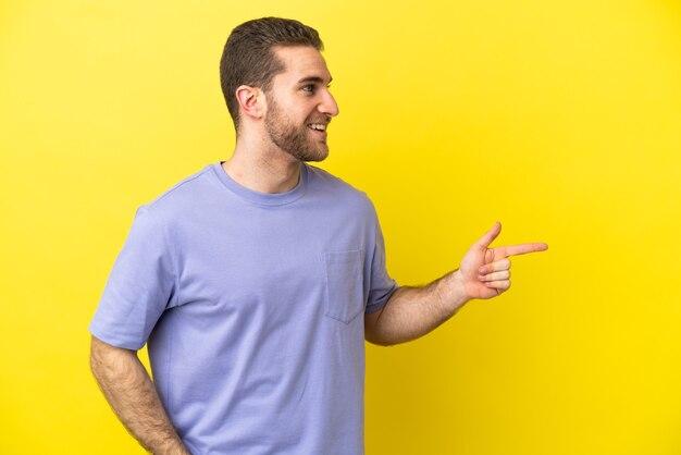 Homem loiro bonito sobre fundo amarelo isolado apontando o dedo para o lado e apresentando um produto