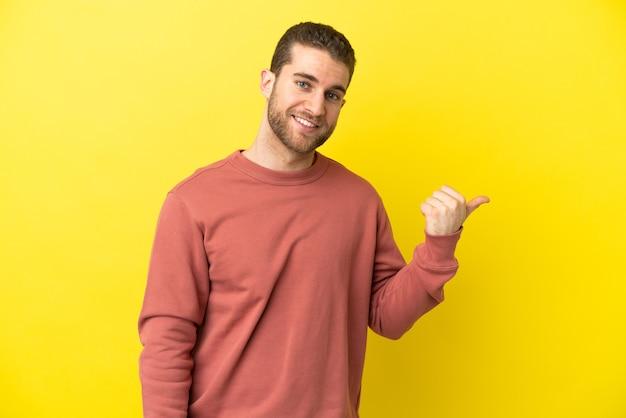Homem loiro bonito sobre fundo amarelo isolado apontando para o lado para apresentar um produto