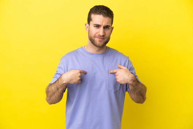 Homem loiro bonito sobre fundo amarelo isolado apontando para si mesmo
