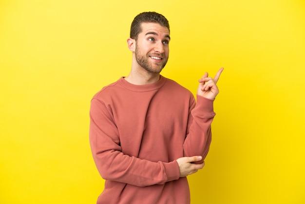 Homem loiro bonito sobre fundo amarelo isolado apontando para uma ótima ideia