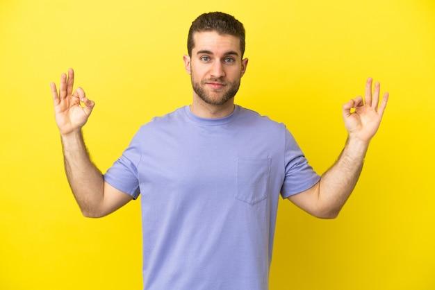 Homem loiro bonito sobre fundo amarelo isolado em pose zen