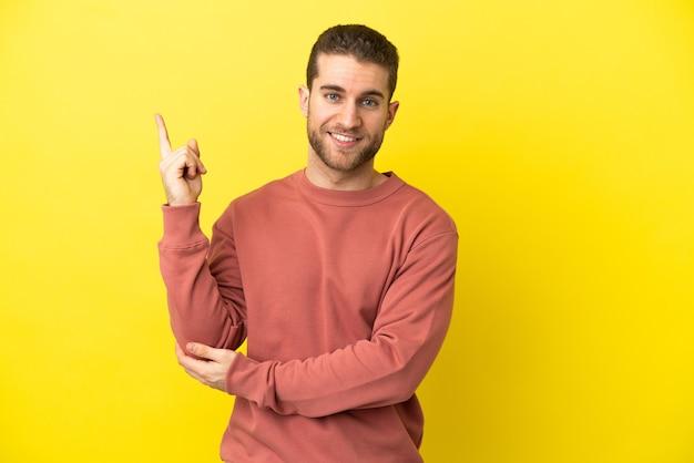 Homem loiro bonito sobre fundo amarelo isolado feliz e apontando para cima