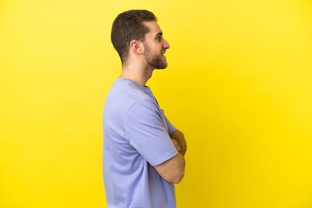 Homem loiro bonito sobre fundo amarelo isolado na posição lateral