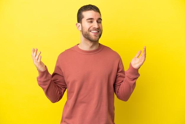 Homem loiro bonito sobre fundo amarelo isolado sorrindo muito