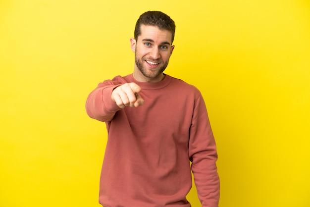 Homem loiro bonito sobre fundo amarelo isolado surpreso e apontando para a frente