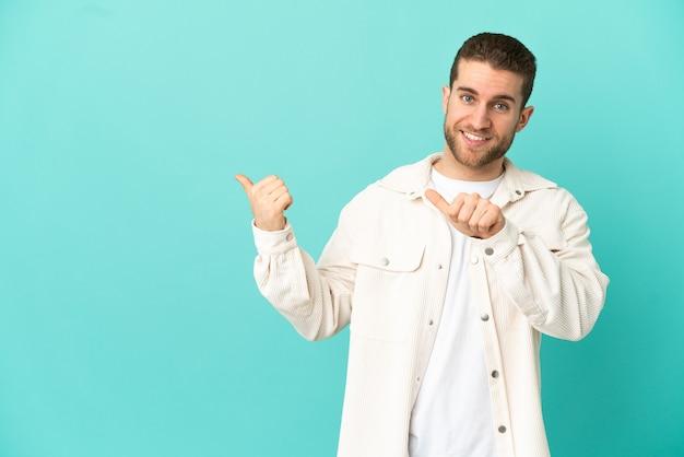 Homem loiro bonito sobre fundo azul isolado apontando para o lado para apresentar um produto