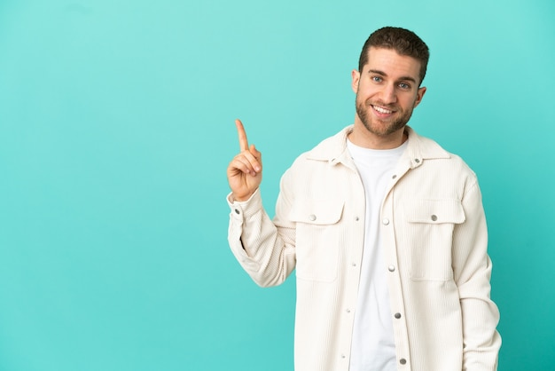 Homem loiro bonito sobre fundo azul isolado mostrando e levantando um dedo em sinal dos melhores